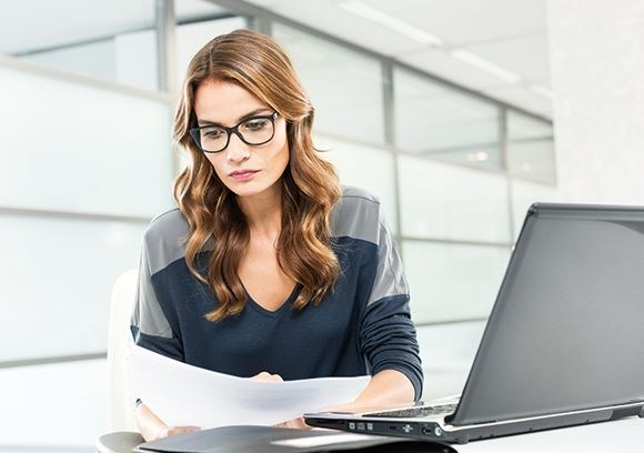 Female sat at a desk wearing a pair of Hoya Vision eyeglass lenses reading from a page