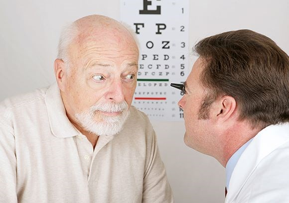 Hoya Vision cataracts optician examining an elderly man's eyes