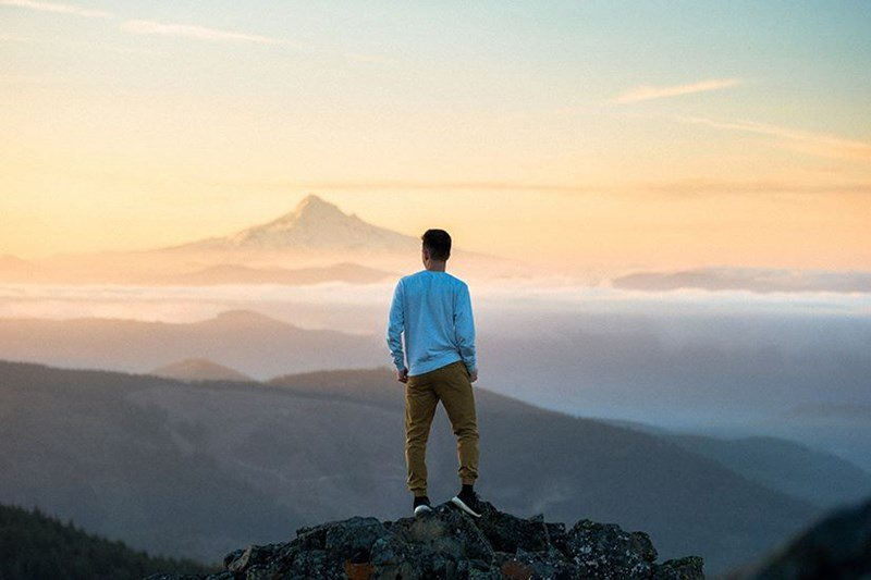 Male stood on a mountain top overlooking other mountains