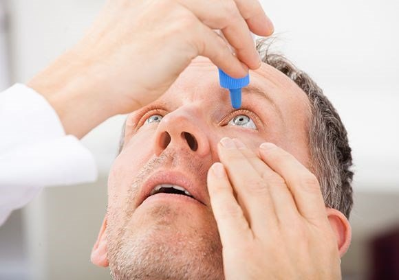 Male using eye drops to combat dry eye syndrome