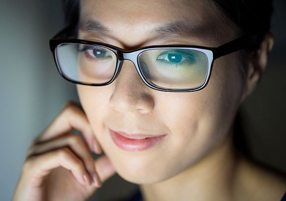 Woman in front of a screen wearing eyeglasses with Hoya Vision lenses