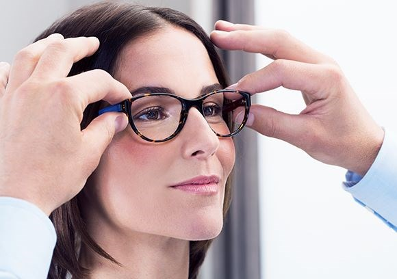 Female having eyeglasses with Hoya Vision lenses fitted by a male optician