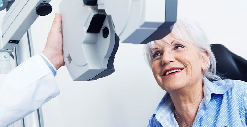 Elderly woman in a blue shirt getting her eyes tested by male optician