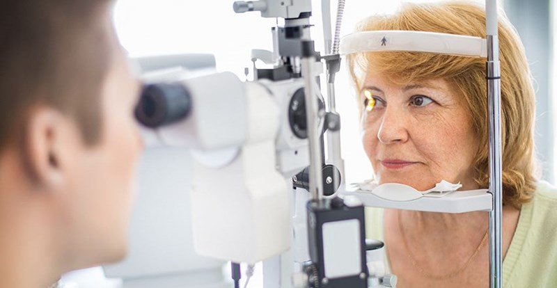 Older woman getting an eye examination by a Hoya Vision optician
