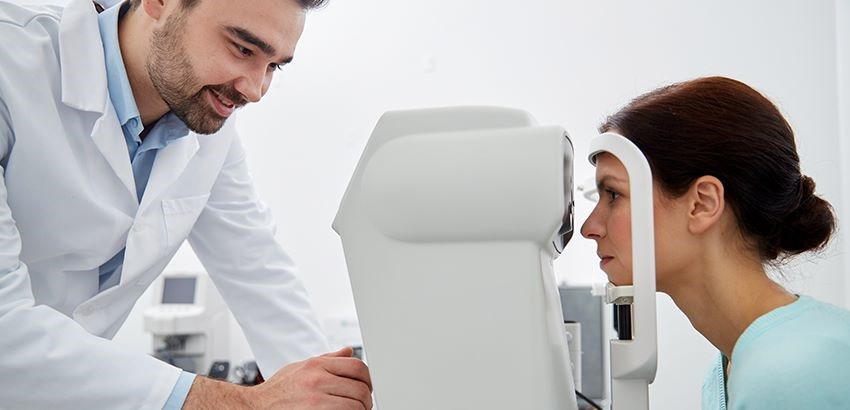 Woman getting an eye scan by a male Hoya Vision optician