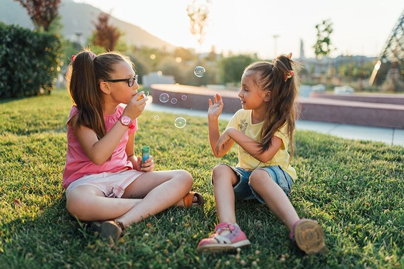 Hoya Vision the ideal lens for kids girls playing with soap bubbles
