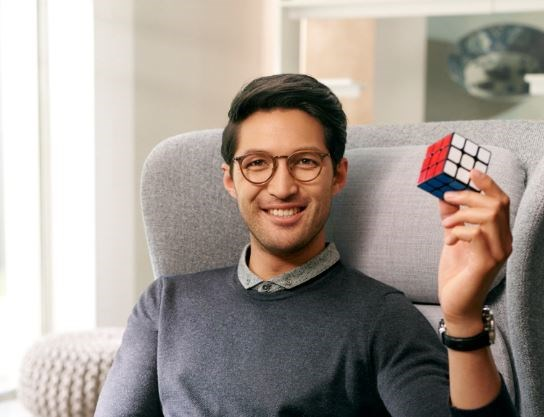 Male wearing eye glasses with Hoya Vision lenses holding a rubik's cube