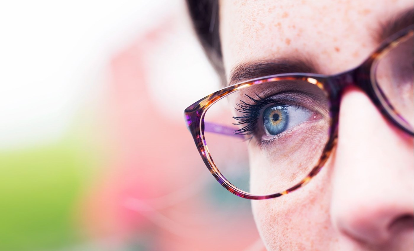 Close up of a woman wearing eyeglasses with Hoya Vision anti reflective lens coating