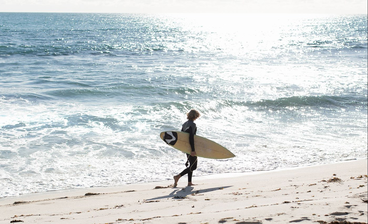Male surfer walking along a beach carrying a surfboard