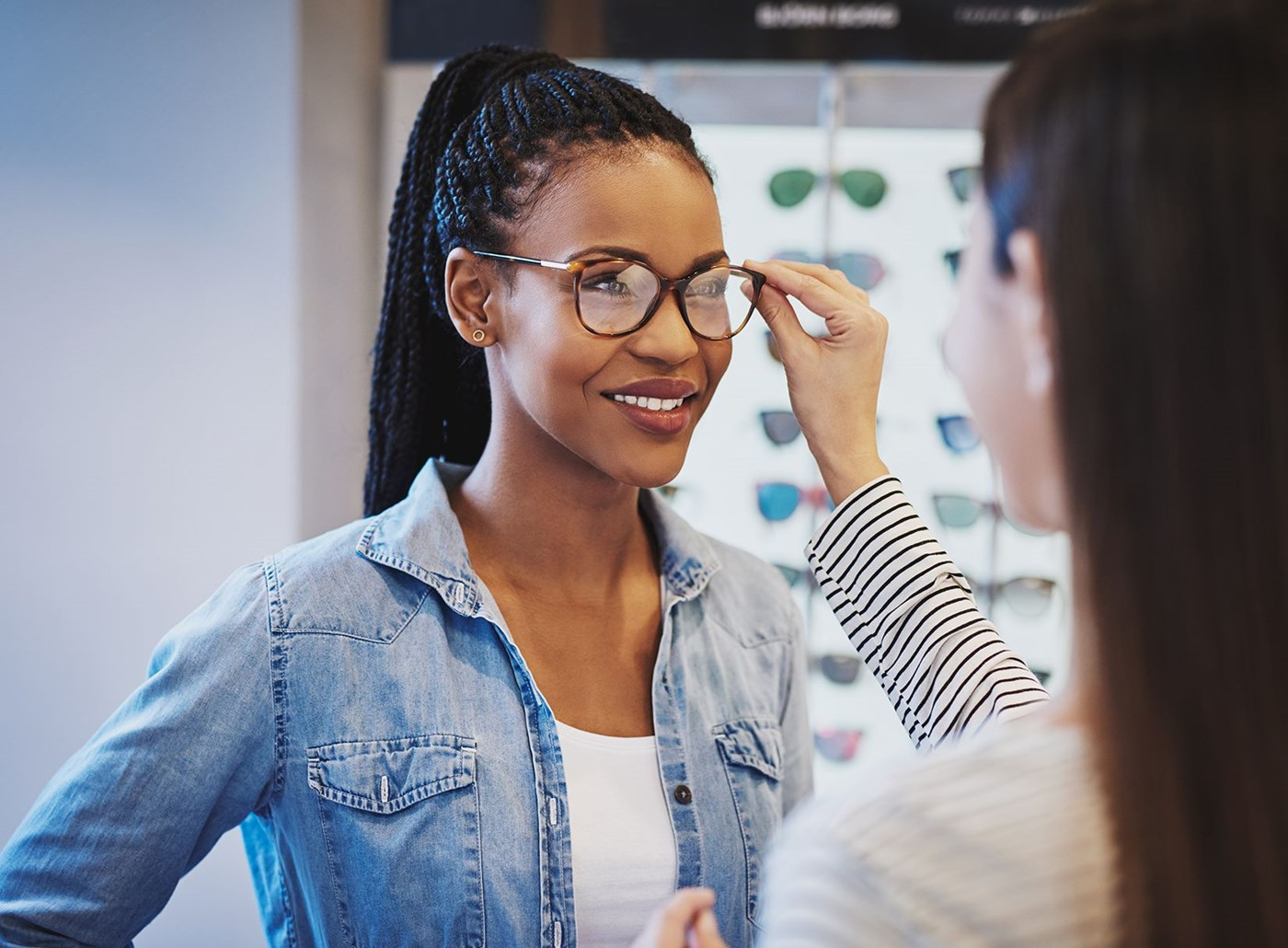 Woman in an optician trying on eyeglasses with Hoya Vision lenses