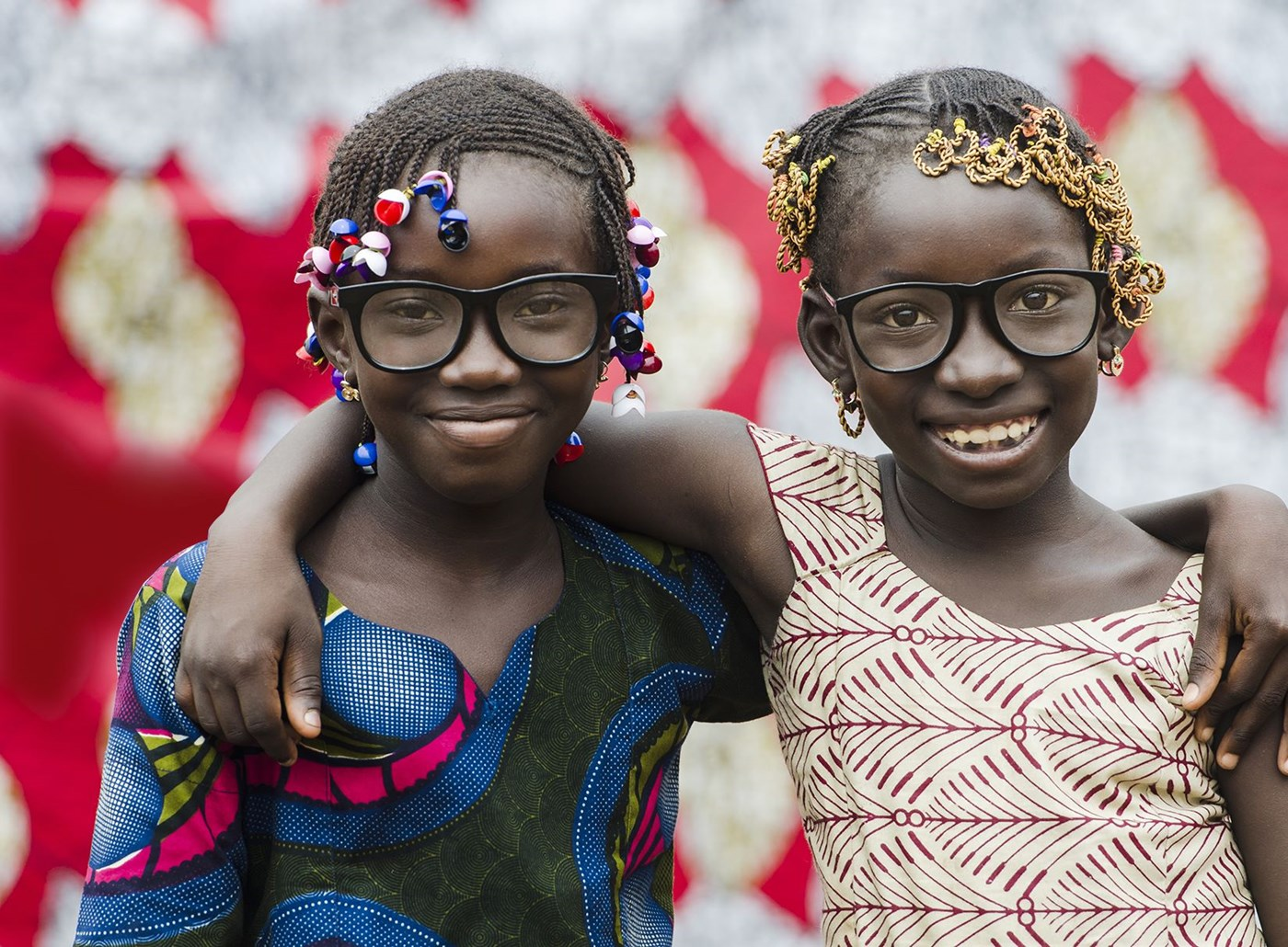 Two girls with braids embracing each other wearing eye glasses with Hoya Vision lenses