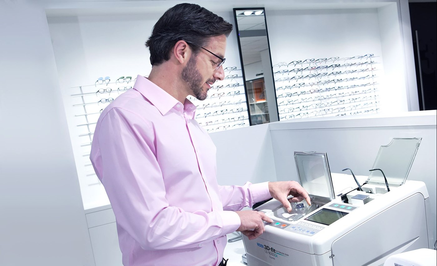 Male Hoya Vision optician in a pink shirt looking into a machine