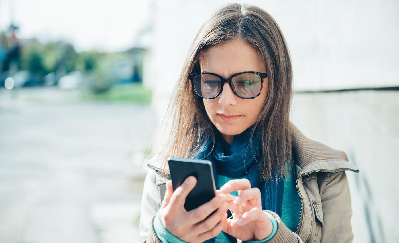 Woman scrolling on her mobile phone wearing eyeglasses with Hoya Vision photochromic lenses