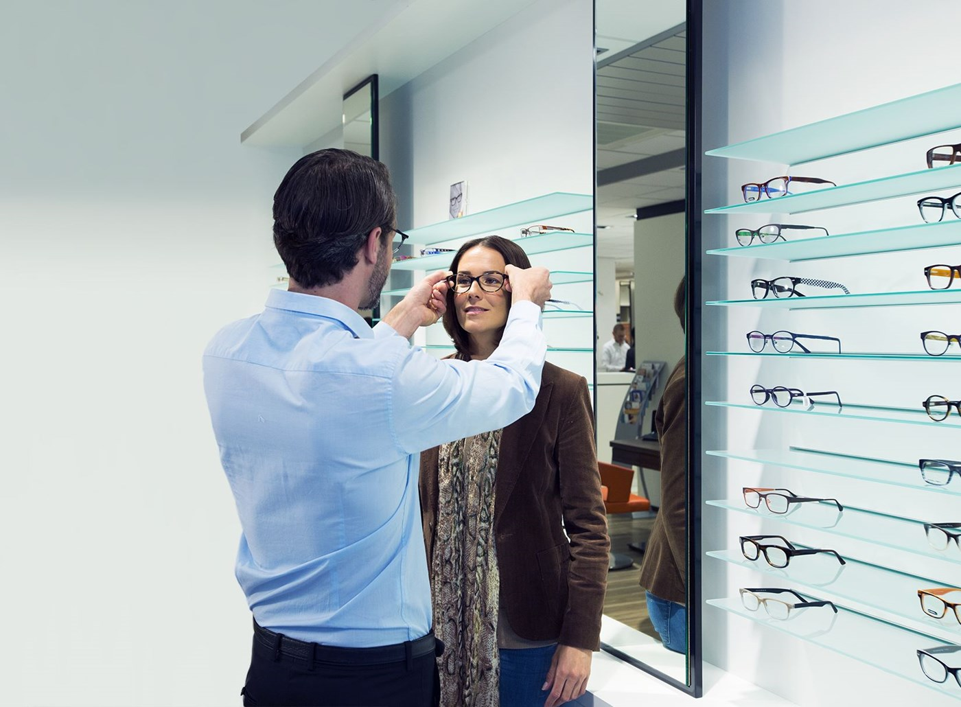 Male Hoya Vision optician placing eyeglasses on a female