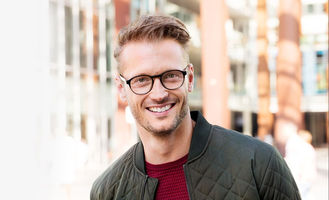 Male wearing dark framed eye glasses smiling