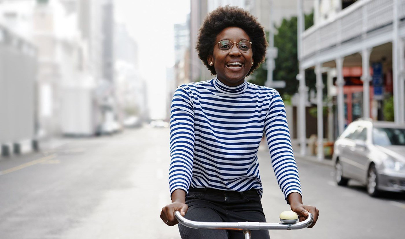 Woman wearing a striped top riding a bicycle wearing eyeglasses with Hoya Vision lenses