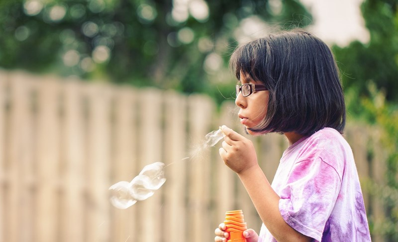 Young girl blowing bubbles wearing eyeglasses with Hoya Vision children's lenses