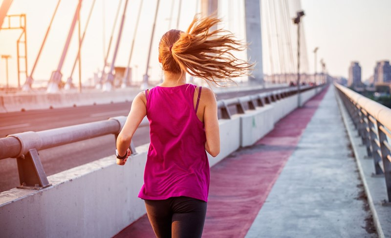 Woman in pink top running along a bridge