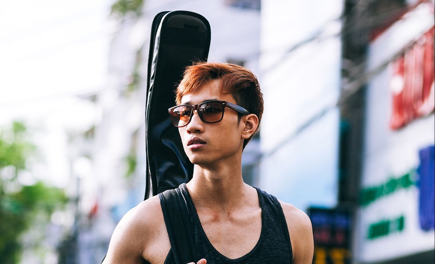 Male wearing glasses with Hoya Vision tinted lenses carrying a guitar on his back