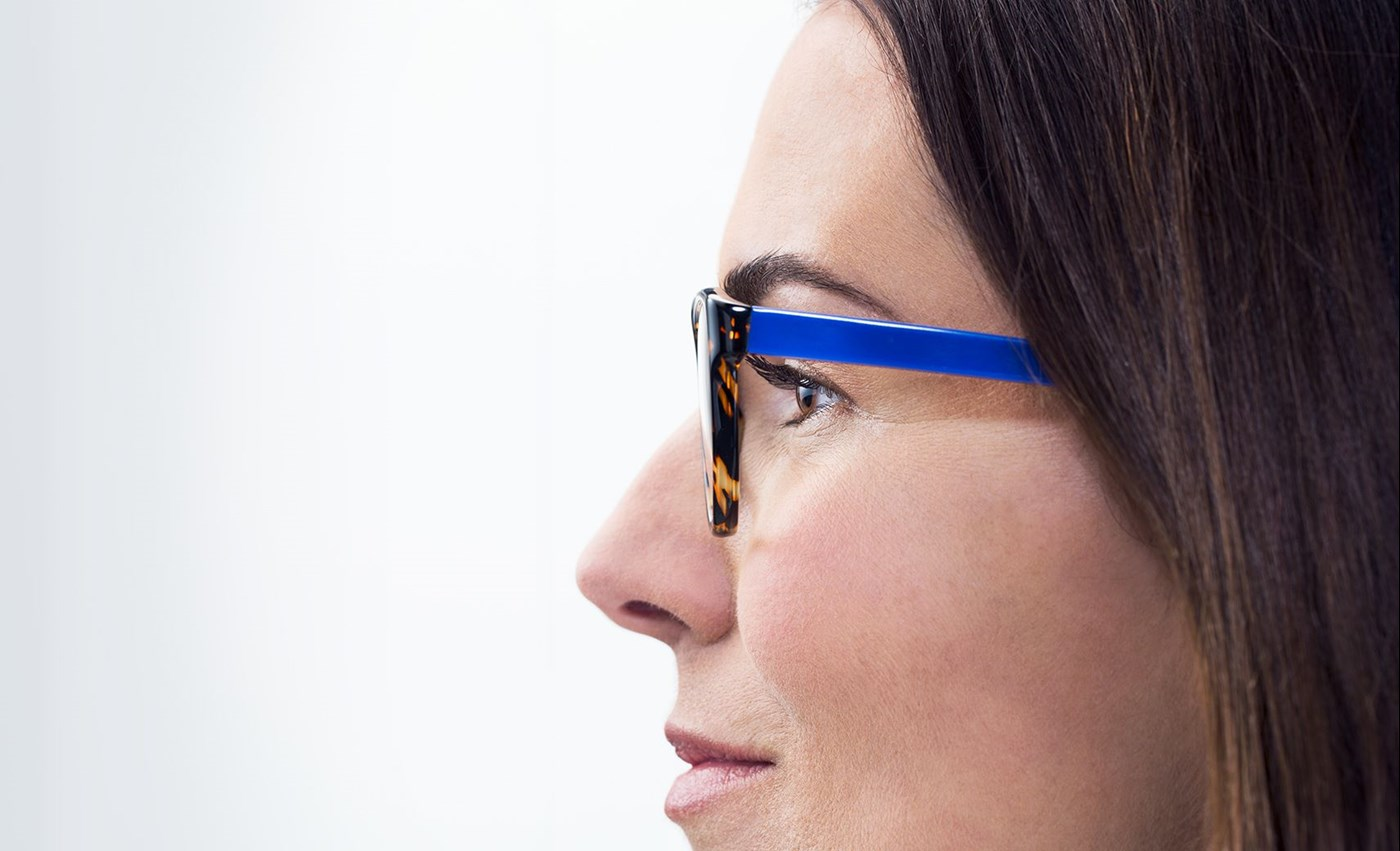Woman wearing blue frames with Hoya Vision lenses