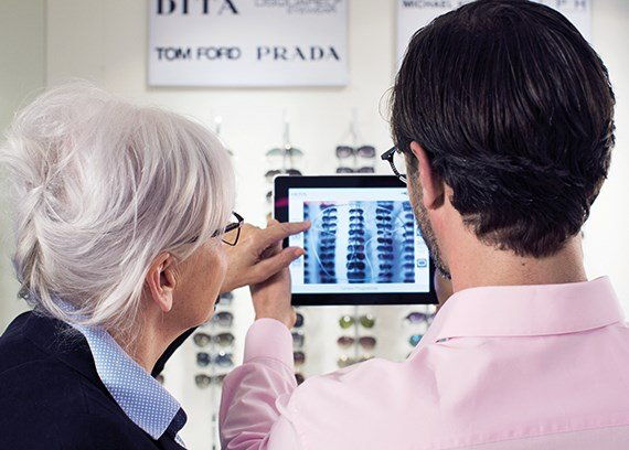 Male and female wearing eye glasses in an optician using an iPad