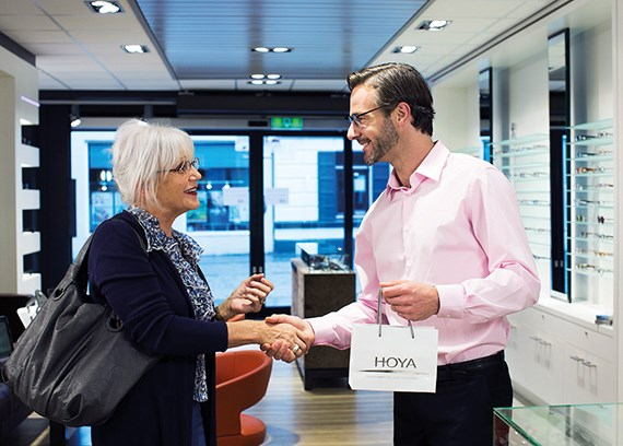 Male Hoya Vision optician shaking older womans hand and giving her a Hoya bag