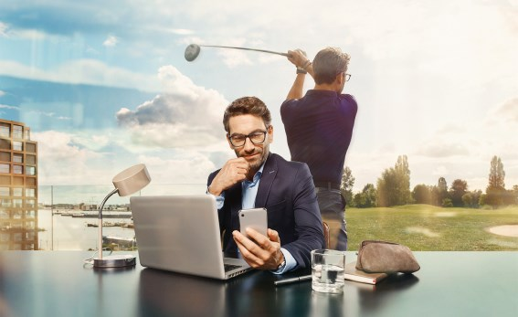 Male wearing Hoya Vision lenses at a desk looking at mobile phone with reflection of himself golfing behind him