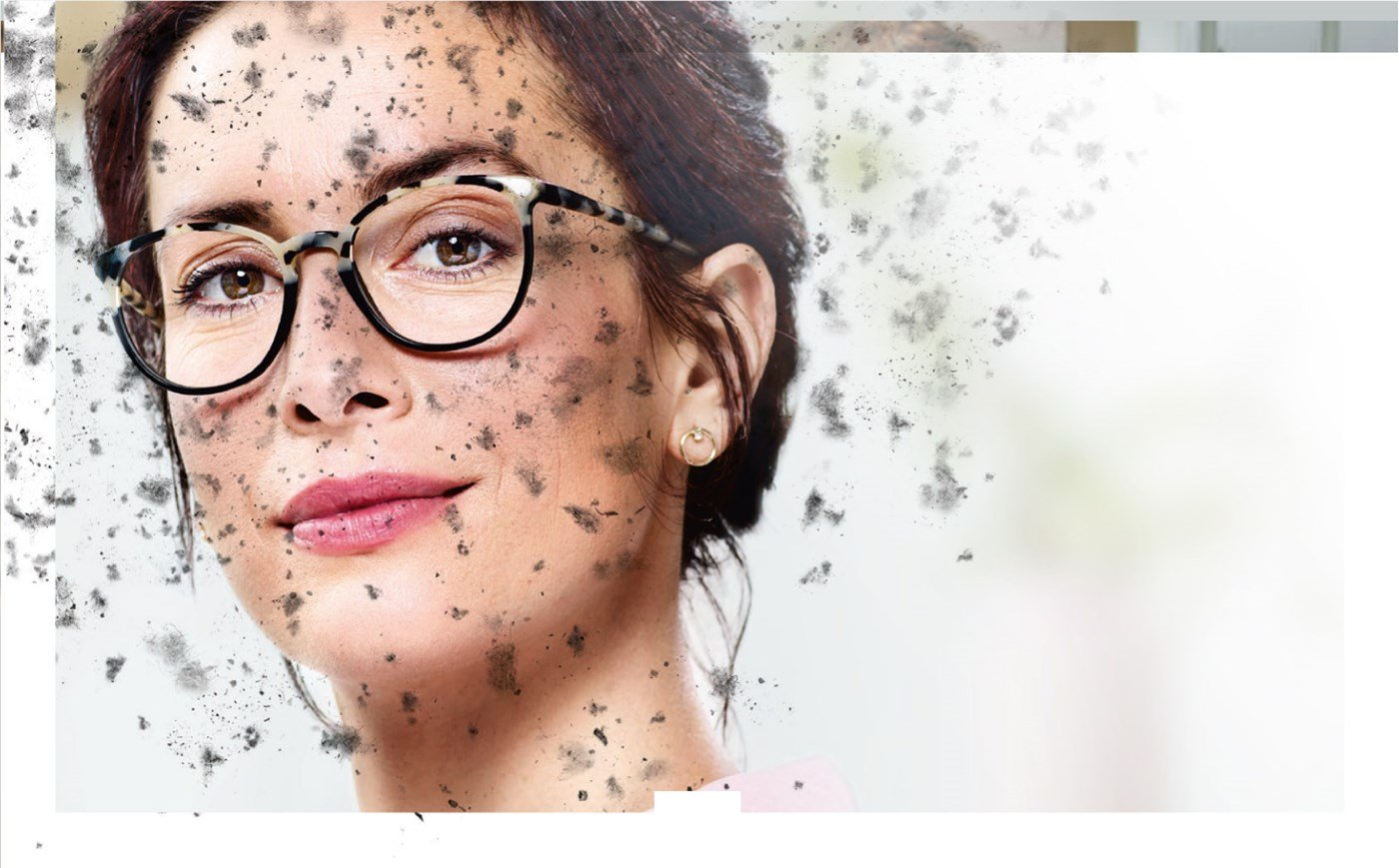 Woman wearing eyeglasses with Hoya Vision lenses behind a dirty screen