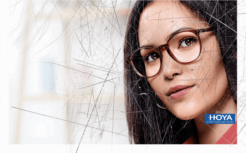 Woman wearing eyeglasses with Hoya Vision lenses behind a scratched screen