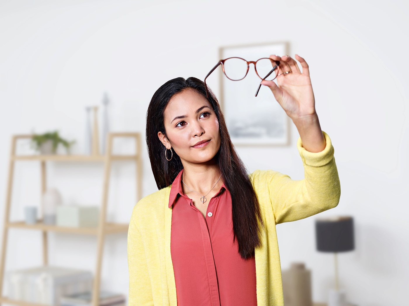 Woman holding eyeglasses up to light looking making sure they are clean
