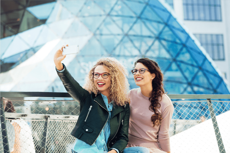 Two females outdoors wearing eyeglasses with Hoya Vision lenses taking a selfie