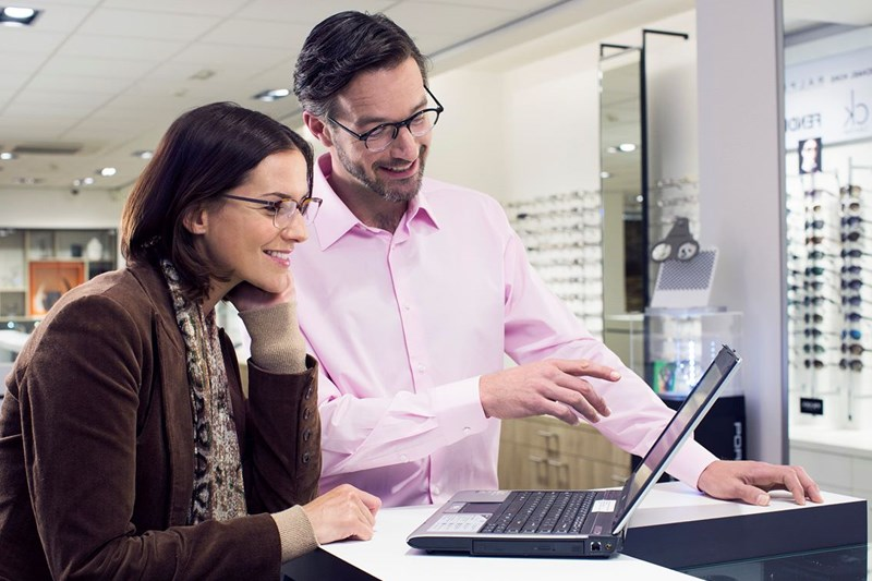 Male Hoya Vision optician beside a female eyeglass wearer pointing to a laptop screen