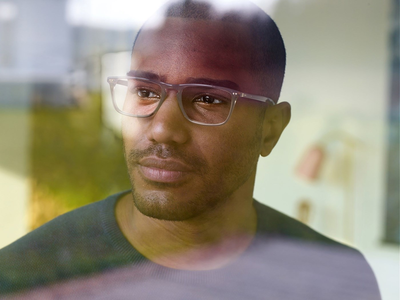 Male wearing eyeglasses with Hoya Vision lenses looking out a window