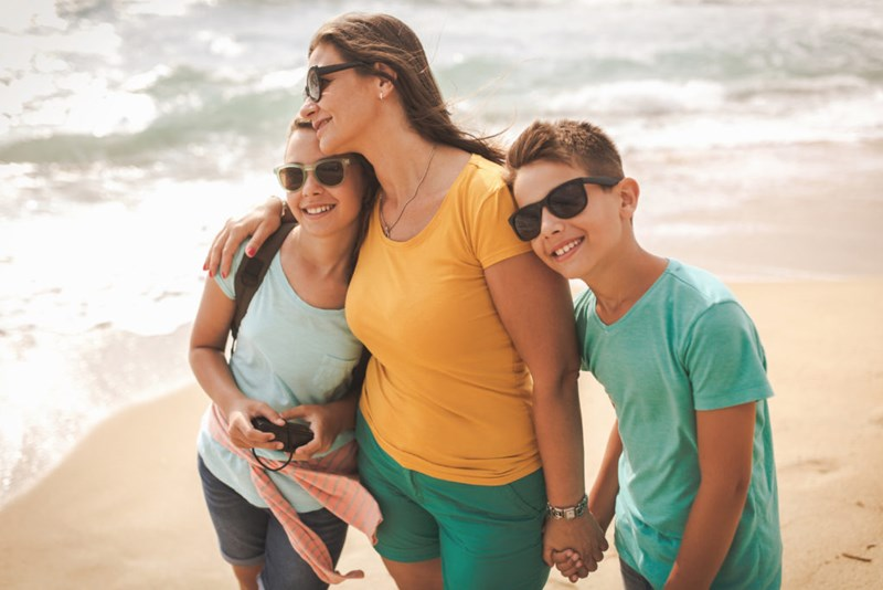 Mother with children all wearing sunglasses on a beach