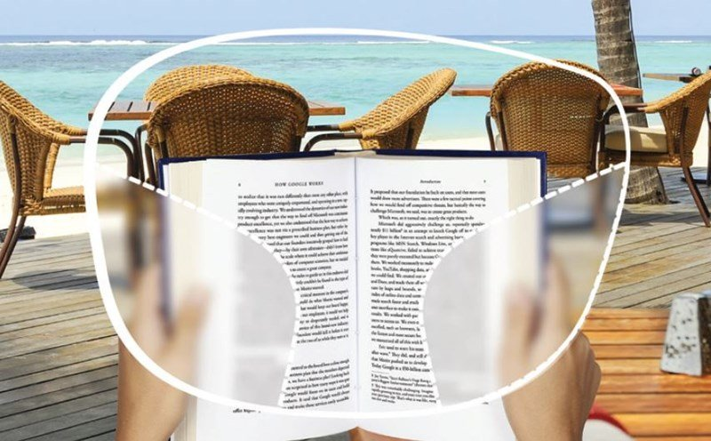 User reading book on holiday through eyeglass frame, clear in centre and blurred at sides