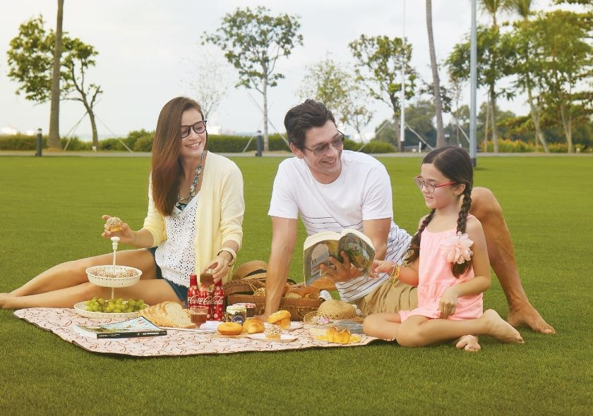 Parents and daughter all wearing eyeglasses having a picnic outdoors