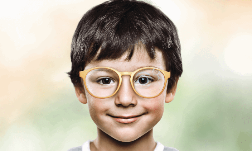 Young boy wearing eyeglasses staring and smiling at camera