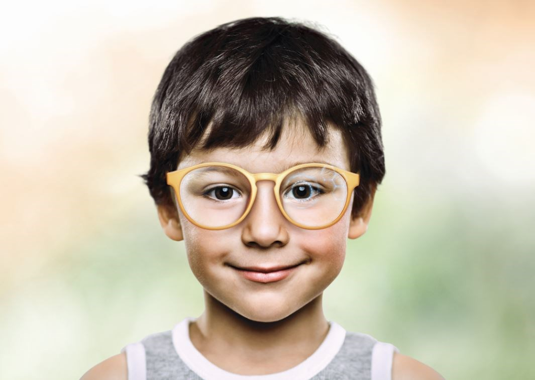 Young boy wearing orange eyeglass frames with myosmart lenses smiling at camera