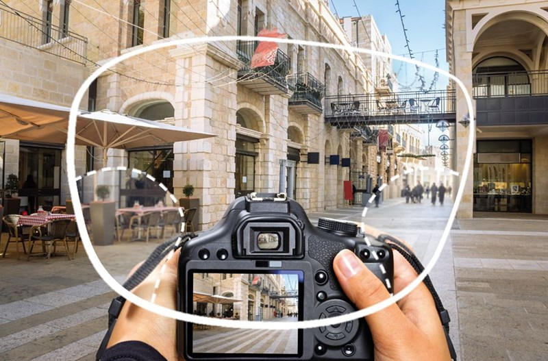User holding camera taking image of street through an eyeglass lens