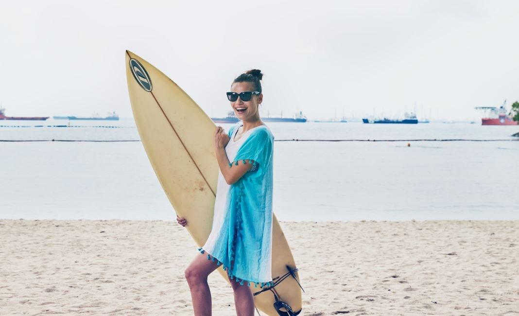 Female surfer in blue beach coverup and sunglasses