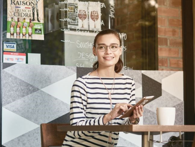 Female sitting outside cafe on tablet wearing glasses