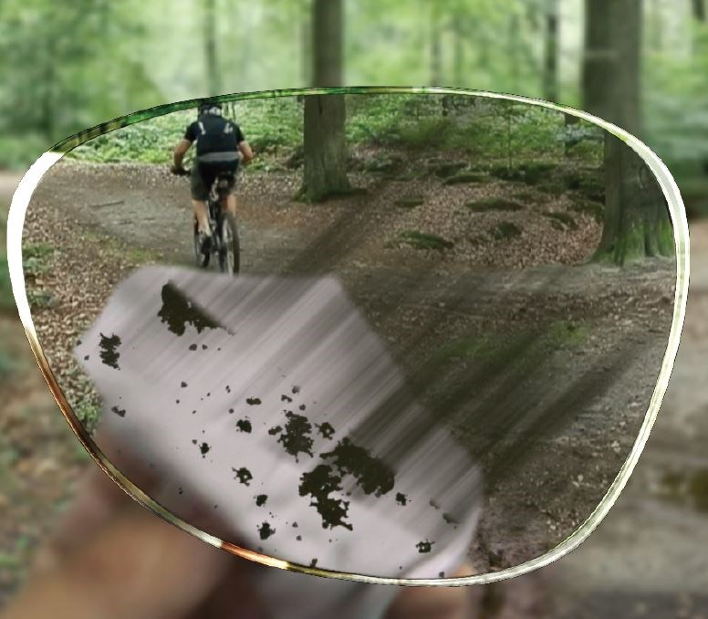 Dirty lens being wiped clean while on mountain bike track