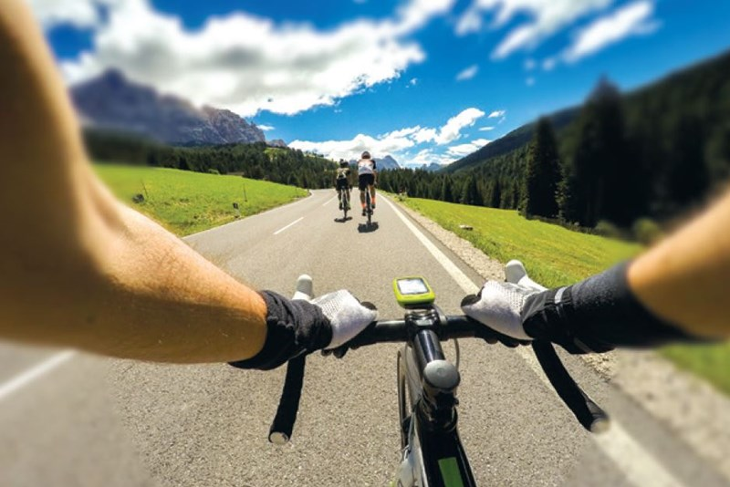View through bike handlebars following two cyclists through mountains