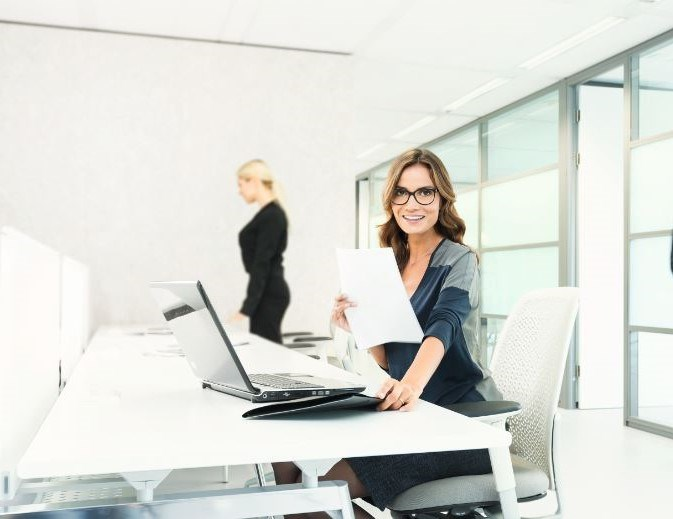 Woman sat at desk wearing eyeglasses holding paper on computer
