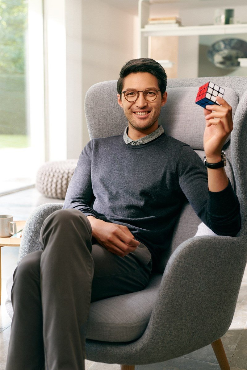 Male sat on chair wearing eyeglasses holding Rubik's cube