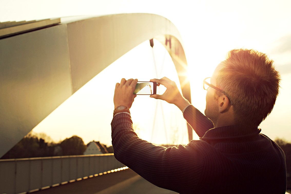 Male wearing eyeglasses taking image of bridge on smartphone