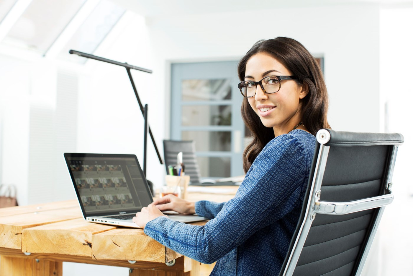 Female sat behind laptop screen wearing eyeglasses