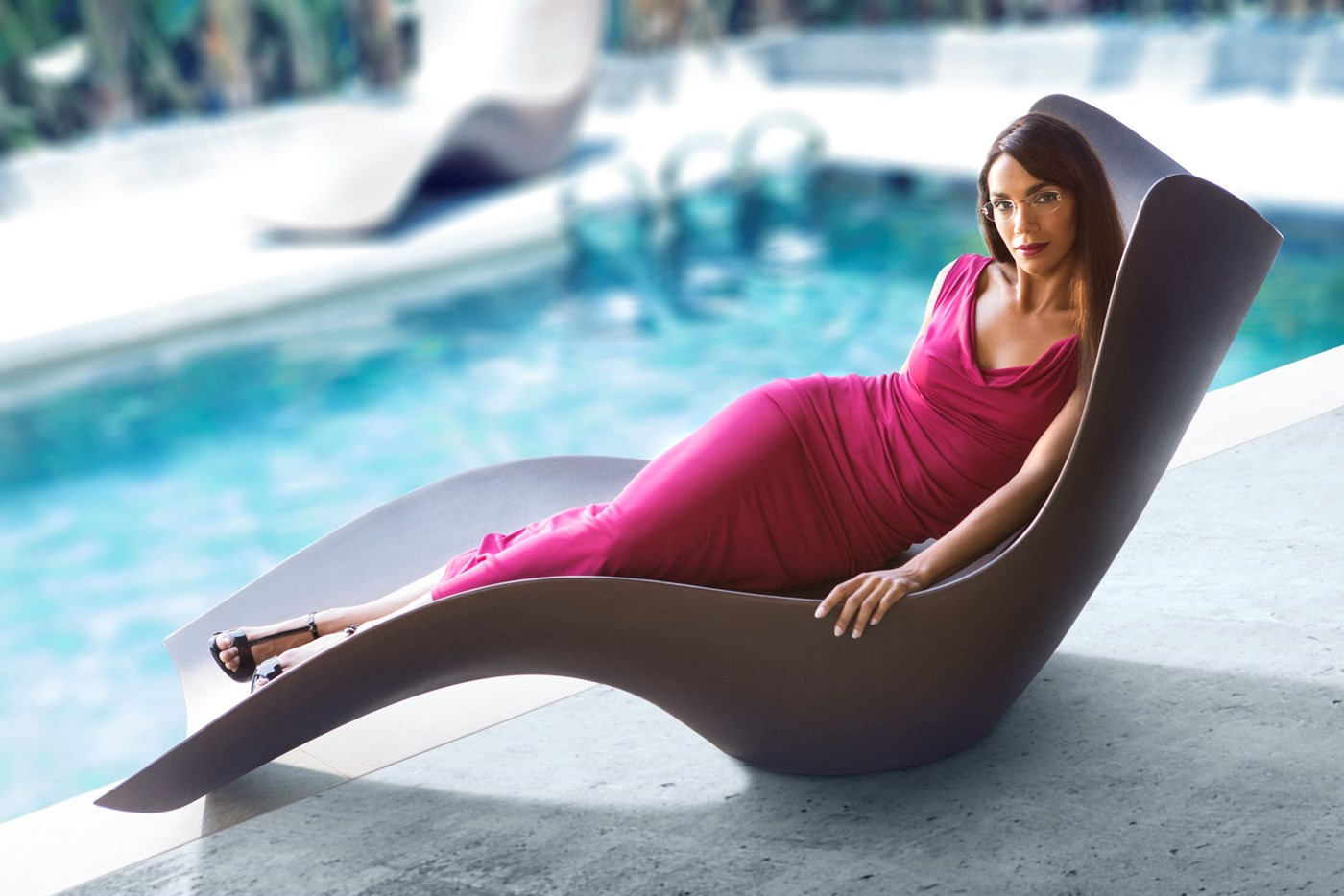 Female lounging on chair beside pool in pink dress wearing eyeglasses