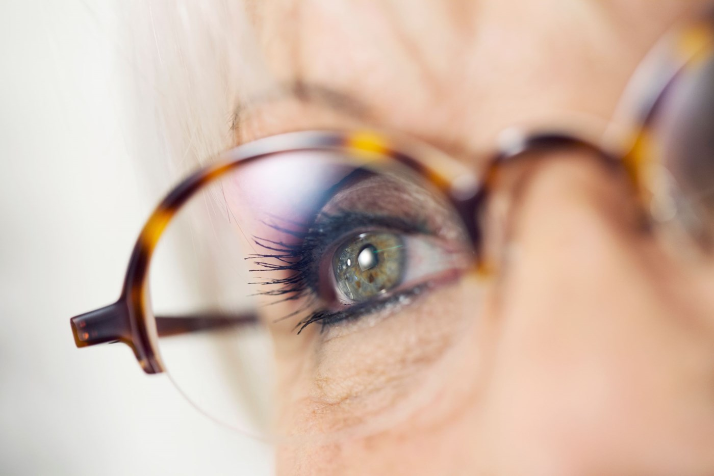 Up close shot of older female eye behind eyeglass lenses