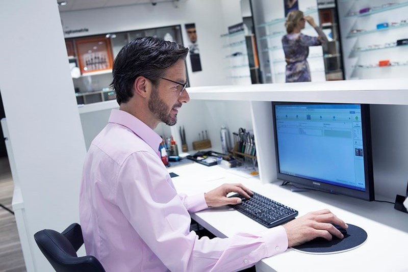 Male in pink shirt using computer